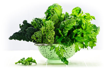 Leafy green veggies in a colander.